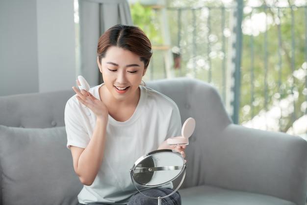 Довольно азиатская женщина, применяя пудру на лице