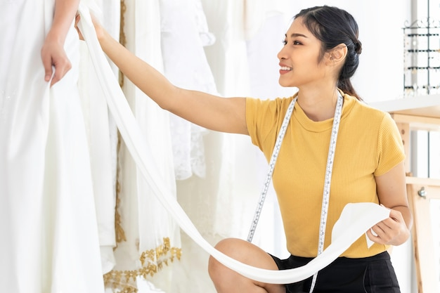 Pretty asian woman choosing dress in a shop with tailor assistant.