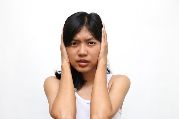 Pretty asian woman covered his ears on white wall