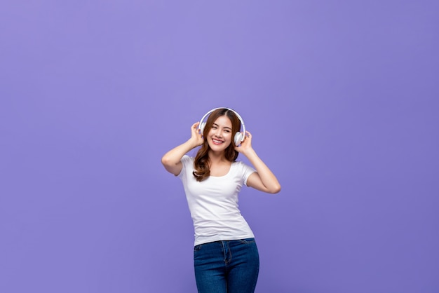 Pretty asian woman dancing and listening to music on headphones