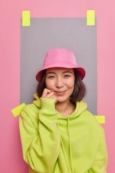 예쁜 아시아 여성은 카메라를 부드럽게 바라보고 뺨에 손을 대고 파나마를 입고 녹색 후드티는 광고 콘텐츠를 위한 빈 카피 공간에 반가운 포즈를 취합니다