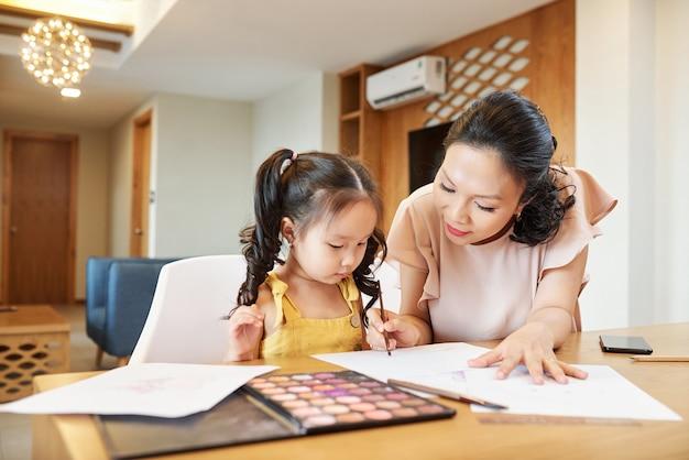 Симпатичная азиатская женщина помогает дочери с рисованием, когда они проводят время дома из-за карантина
