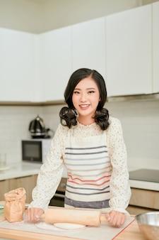 プロのキッチンでかなりアジアの女性が小麦粉で生地を準備します