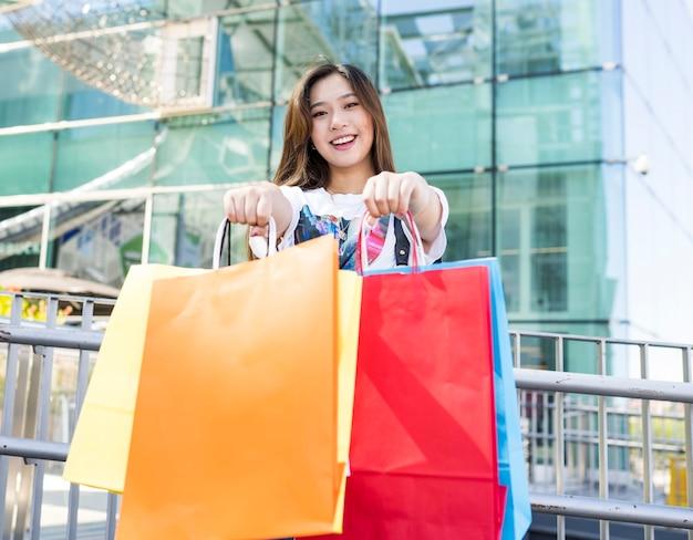 通りで買い物をするカジュアルな服装のかなりアジアの女性