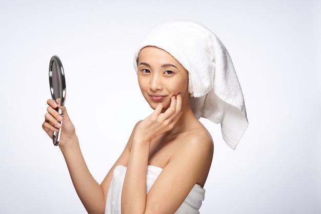 Довольно азиатская женщина в зеркале в полотенце брюк на чистой коже головы омоложения. фото высокого качества