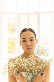 창 근처에 앉아 흰색 상단에 예쁜 아시아 여자