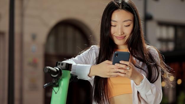 かなりアジアの女性は、電動スクーターの近くでスマートフォンを使用して電動キックスクーターの女性のテキストsmsに乗った後にスマートフォンを使用しています