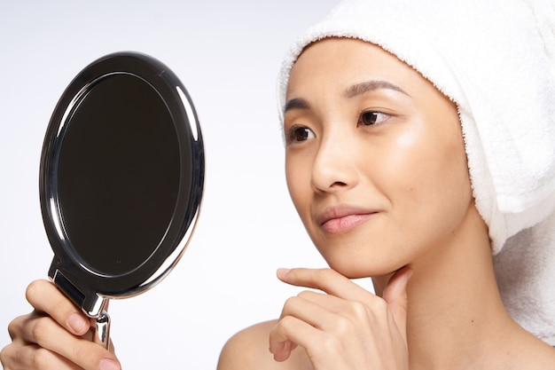 Pretty asian woman looks in the mirror face close-up clean skin
