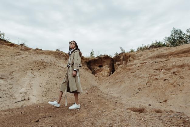 彼女のベージュのマントの砂の採石場でフルハイトをポーズするかなりアジアの女性。