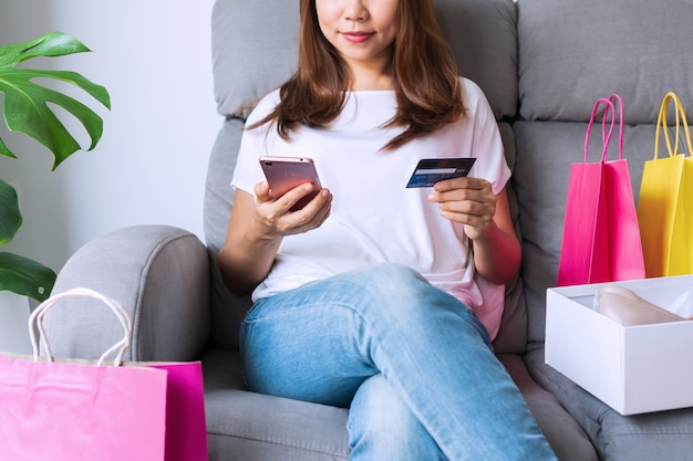 Pretty asian woman sitting on sofa with her fashion items of online shopping parcel and holding smart phone and credit card. shopping online concept.