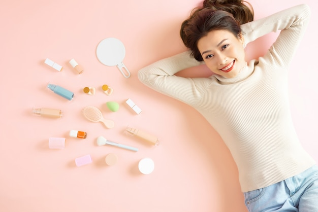 Pretty asian woman smiling while lying on pink floor with her cosmetic makeup tools