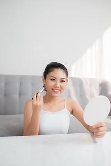 메이크업 브러시를 사용하고 거울을 보고 있는 예쁜 아시아 여성
