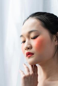 化粧をしているかなりアジアの女性