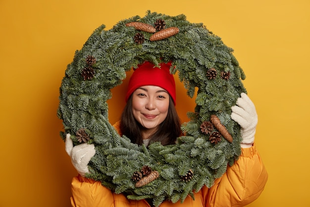 Pretty asian woman wears warm headgear and gloves, looks through handmade traditional christmas wreath, being in good festive mood, anticipates for winter holidays, isolated on yellow studio wall