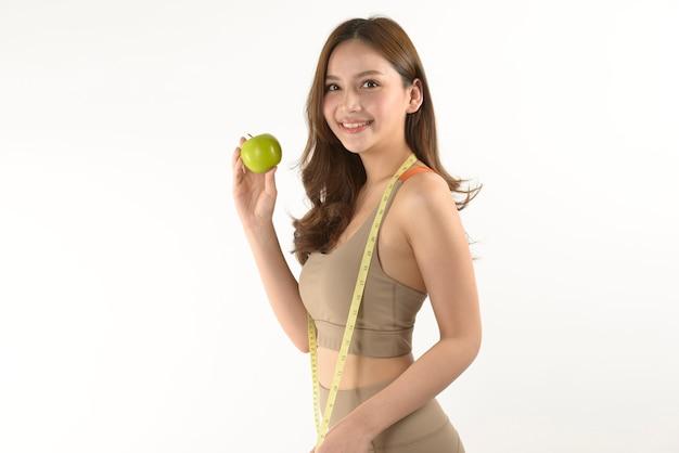 Довольно азиатская женщина с яблоком и рулетка на белом