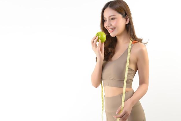 Довольно азиатская женщина с яблоком и рулеткой