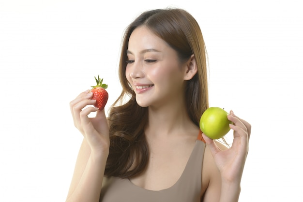 Pretty asian woman with apple and strawberry