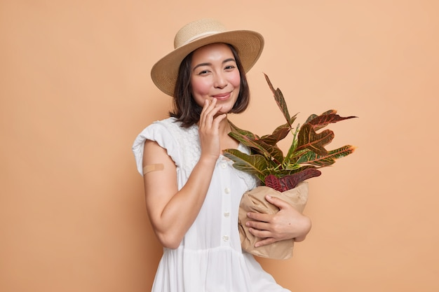 Pretty asian woman with dark hair carries potted houseplant has gentle expression wears fedora and white dress