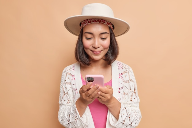 Pretty asian woman with dark hair holds modern mobile phone checks message connected to wireless internet wears fedora knitted white coat isolated over beige wall uses cellular application