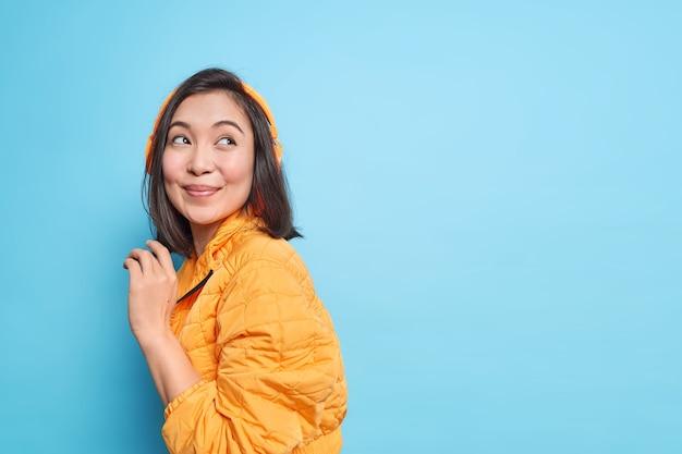 검은 머리를 가진 예쁜 아시아 여자가 옆으로 실내는 음악을 듣기 위해 귀에 무선 헤드폰을 착용하고 파란색 벽 위에 절연 주황색 재킷을 입은 좋은 음질을 즐깁니다.