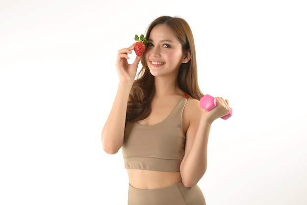 Pretty asian woman with dumbbell and strawberry on white