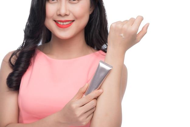 彼女の手にクリームを適用するかなりアジアの若い女性