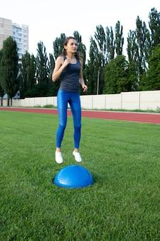 Довольно спортивная брюнетка женщина тренируется с мячом босу на стадионе