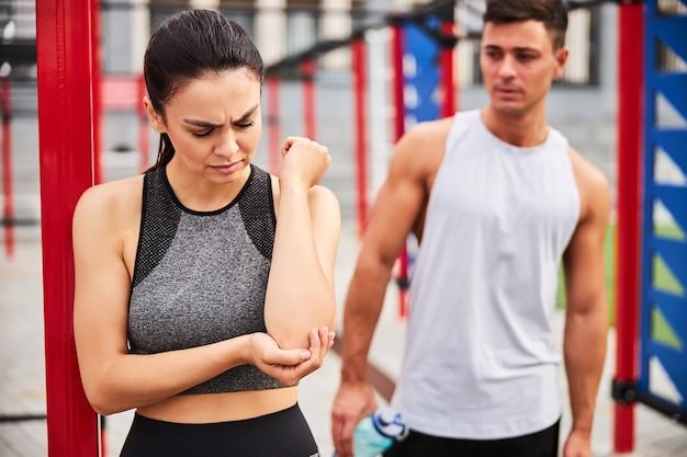 그녀는 운동장에서 근육질의 남자와 운동하는 동안 예쁜 운동 여성이 팔꿈치를 아프게 잡고 있습니다.