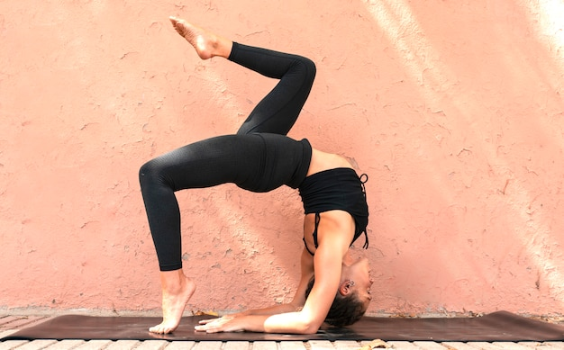 Pretty athletic woman athlete doing extreme yoga poses