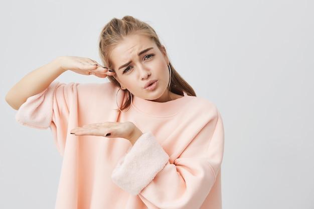 手で何かのサイズを示し、積極的に身振りをし、顔をしかめ、ポーズをとっているスタイリッシュなピンクの長袖のトレーナーを身に着けているかなり魅力的な魅力的な女の子。