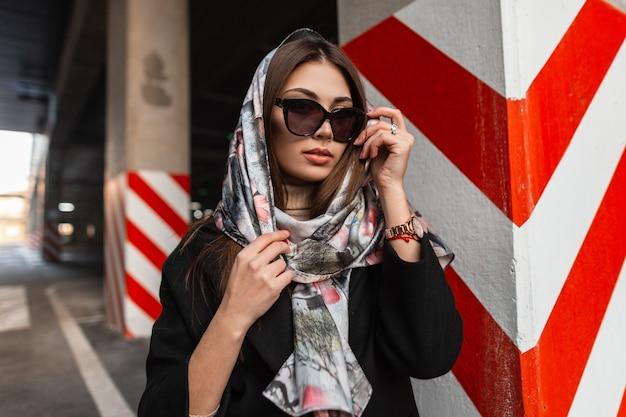 現代の赤白の柱の近くで屋外でポーズをとるコートの頭にスタイリッシュなシルクスカーフのファッショナブルなサングラスでかなり魅力的なファッションモデルの若い女性。市内のプロのビジネスガール。