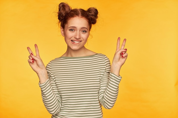2 つのお団子を持つきれいで魅力的な生姜の女性。縞模様のセーターを着て、両手でピースサインを見せて、唇をかむ