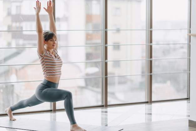 Pretty attractive girl doing yoga and relaxing in the bright room