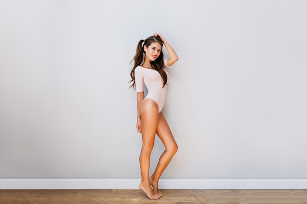 Pretty attractive girl in pink bodysuit in modern apartment. joyful young woman with long brunette hair smiling with red lips  on white wall . good morning, chilling time.