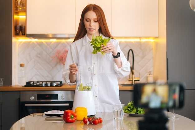 꽤 매력적인 빨간 머리 여성 블로거 건강한 야채 만들기에 대한 비디오 음식 블로그 촬영