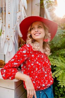 Довольно привлекательная стильная блондинка улыбается женщина в соломенной красной шляпе и блузке, летний модный наряд кафе