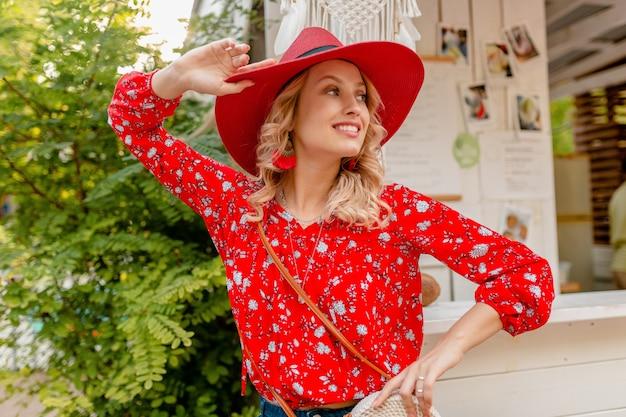 わらの赤い帽子とブラウスの夏のファッションの衣装でかなり魅力的なスタイリッシュな金髪の笑顔の女性