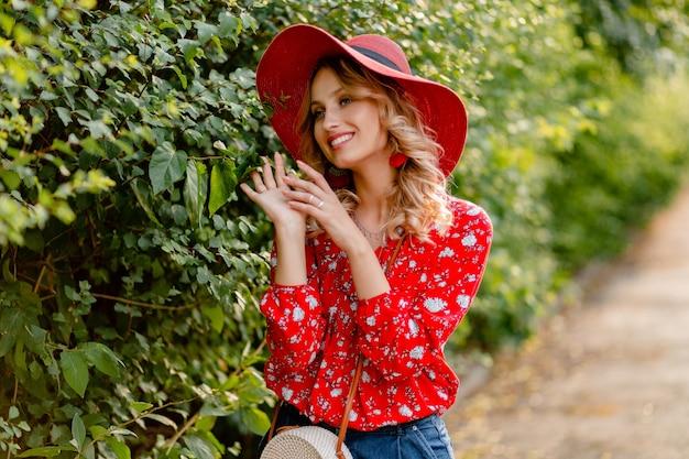 Довольно привлекательная стильная блондинка улыбается женщина в соломенной красной шляпе и блузке летней моды