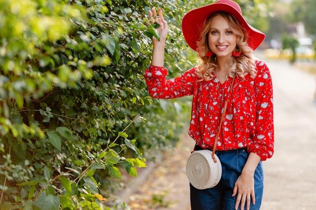 Donna sorridente bionda elegante abbastanza attraente in cappello rosso di paglia e vestito di moda estiva camicetta