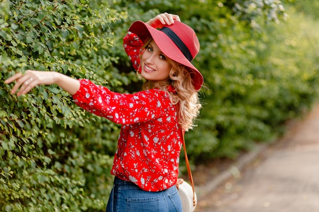 Pretty attractive stylish blond smiling woman in straw red hat and blouse summer fashion outfit