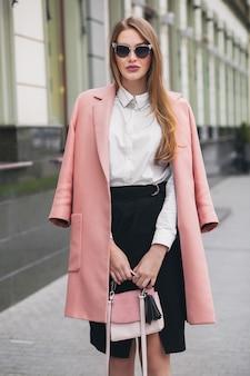 핑크 코트에 도시 거리를 걷는 꽤 매력적인 세련된 웃는 부자 여자