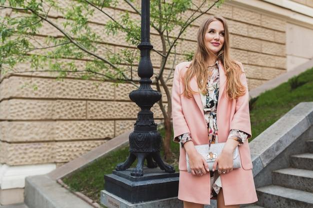 ピンクのコートで街を歩いて、財布を保持しているかなり魅力的なスタイリッシュな笑顔の女性