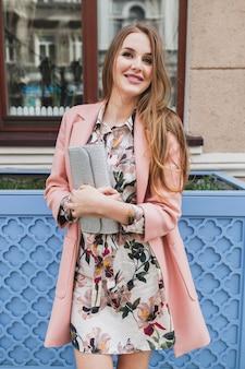 イヤホンで音楽を聞いて、財布を持ってピンクのコート春のファッショントレンドの街を歩いてかなり魅力的なスタイリッシュな笑顔の女性