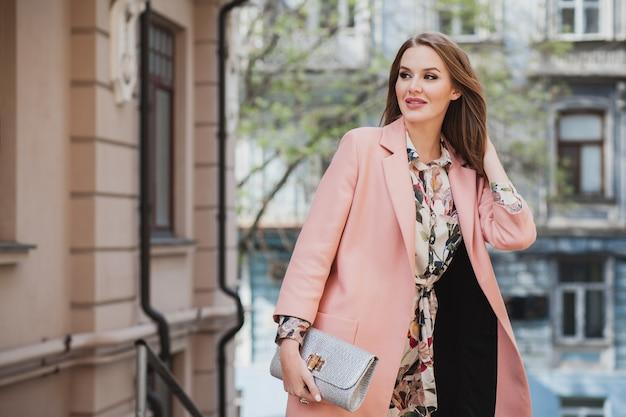 ピンクのコートで街を歩いてかなり魅力的なスタイリッシュな笑顔の女性