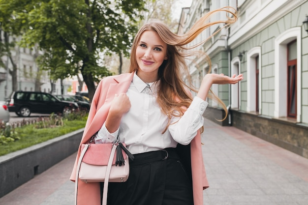 Pretty attractive stylish smiling woman walking city street in pink coat spring fashion trend holding purse, elegant style, waving long hair