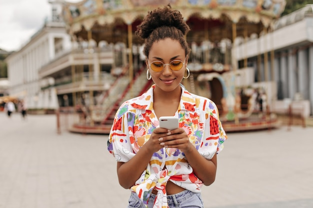 Pretty attractive woman in denim pants, colorful bright shirt and orange sunglasses holding phone and messaging outside