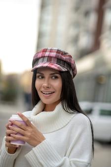 Довольно привлекательная женщина, держащая чашку, попивая кофе на улице