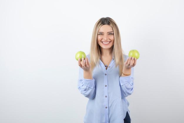 新鮮なリンゴを立って保持しているかなり魅力的な女性モデル。