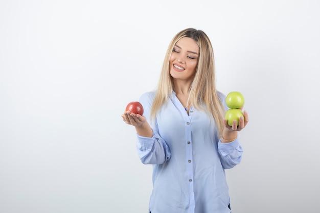 Довольно привлекательная модель женщины стоя и держа свежие яблоки.