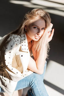 빈티지 청바지에 유행 재킷에 꽤 매력적인 젊은 여성 패션 모델 금발 회색 스튜디오에 앉아 따뜻한 봄 햇살을 즐깁니다